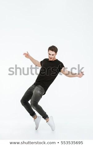 young man dancing over black Stock photo © julenochek