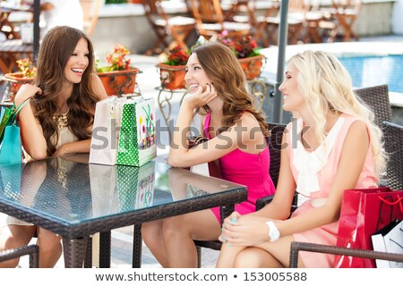 A young woman sitting in a cafe with shopping bags drinking tea Stock photo © monkey_business