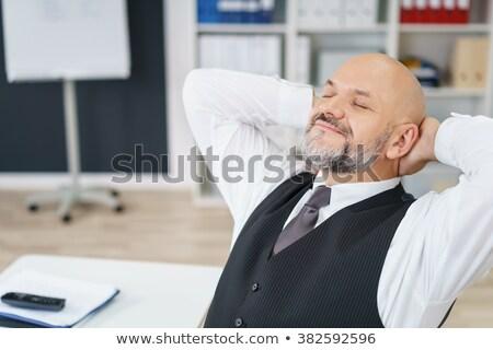 homem · inclinando-se · para · trás · cadeira · sorridente · negócio · escritório - foto stock © is2