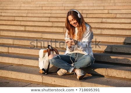Brunette woman sitting on stairs  while listning music and using Stock photo © boggy