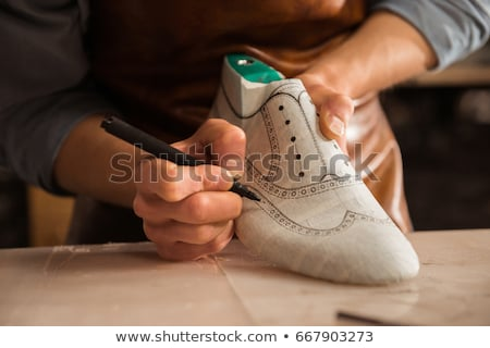 Shoemaker making handmade shoes in workshop. Stock photo © RAStudio