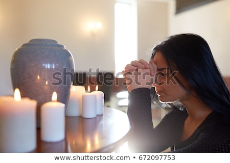 sad woman with funerary urn praying at church Stock photo © dolgachov