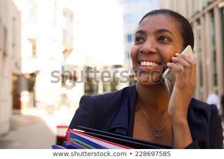 African secretary with folders talking on phone stock photo © studioworkstock