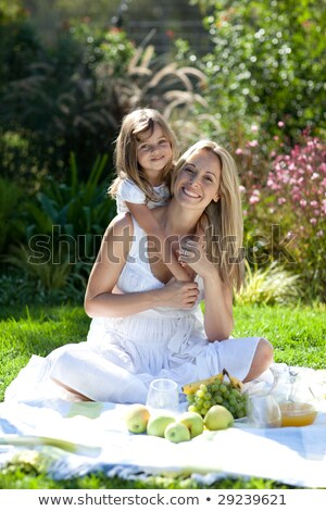 A Middle Eastern woman and her daughter sitting in a park Stock photo © monkey_business