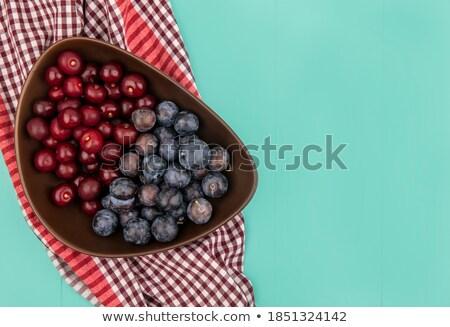 Bowl of cherries on checked tablecloth Stock photo © IS2