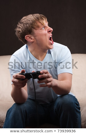 Portrait of happy young man yelling while playing video games on Stock photo © deandrobot