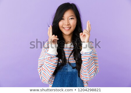 portrait of a lovely young asian woman isolated over violet background holding fingers crossed for stock photo © deandrobot