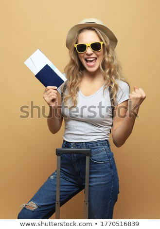 Emotional young woman posing isolated over pink background wall holding passport and tickets. Stock photo © deandrobot