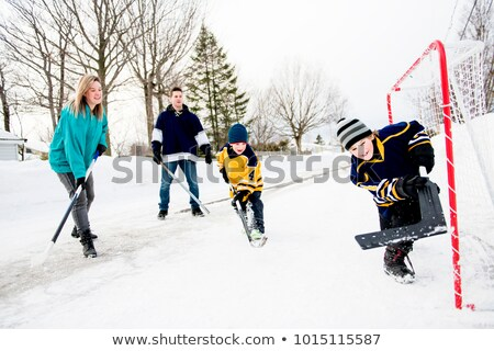 happy funny kids playing hockey with father and mother on street in the winter season stock photo © lopolo