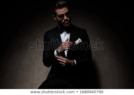 cool young businessman fixing his tie and looks away  Stock photo © feedough