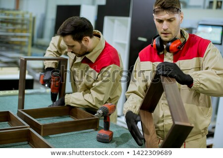 Two young workers assembling furniture in the factory Stock photo © boggy