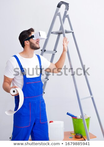 The man with vr glasses gluing wallpaper Stock photo © Elnur