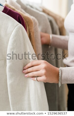 Hand of young woman holding by sleeve of jacket from new seasonal collection Stock photo © pressmaster