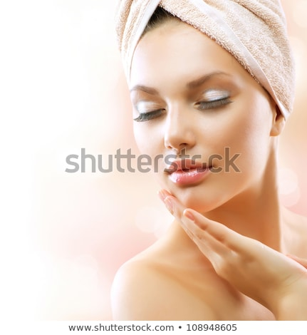 Fresh young beautiful woman with white towel on head applying her facial cream Stock photo © pressmaster