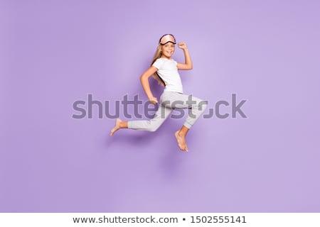 happy woman in pajama and eye mask jumping Stock photo © dolgachov