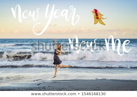 NEW YEAR NEW ME concept A young woman launches a kite on the beach. Dream, aspirations, future plans Stock photo © galitskaya