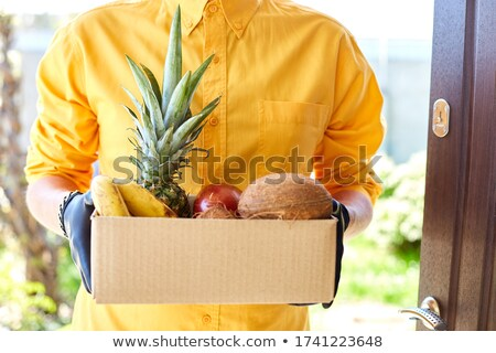 Courier man delivery box with exotic fruits food, contactless delivery. Stock photo © Illia