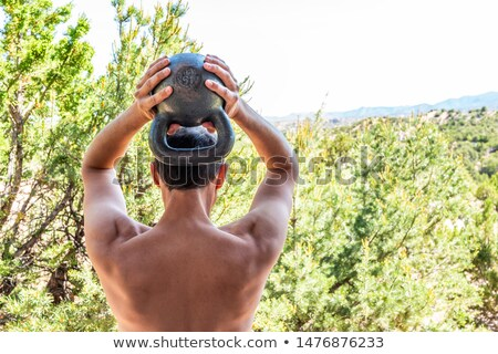 Young man doing kettlebell exercise outside in park Stock photo © Ammentorp