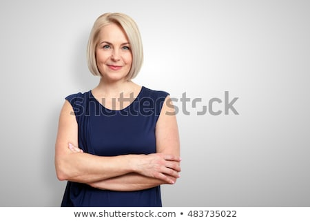 smiling aged lady with folded arms stock photo © stockyimages