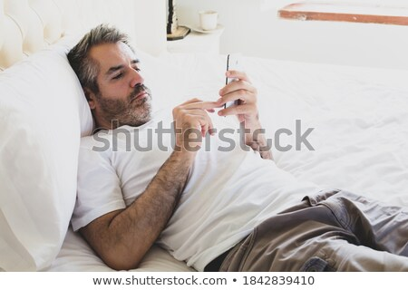 Man luxueus bed messaging vrienden Stockfoto © stockyimages
