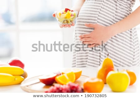 pregnant woman holding a plate of apples stock photo © photography33
