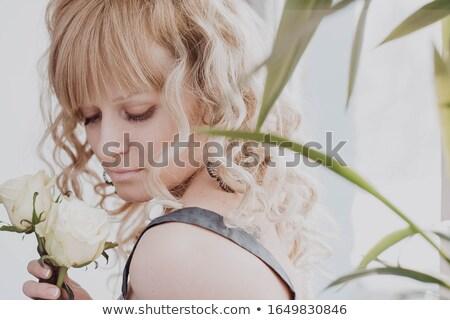 blonde woman with curly hair among greenery stock photo © konradbak