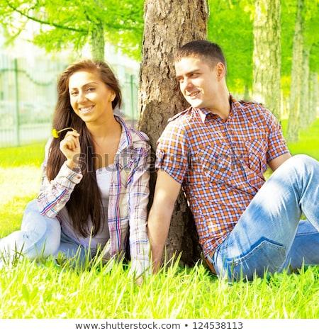 Couple sitting against tree trunk Stock photo © monkey_business
