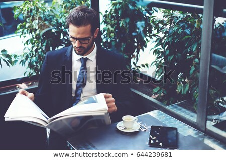 businessman reading newspaper cafe stock photo © hasloo