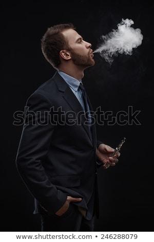 elegante · homem · de · negócios · cigarro · mão · olhando · para · baixo - foto stock © feedough