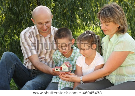 Family in early fall park. father, mother, little boy and girl is sitting on the grass near osier an Stock photo © Paha_L