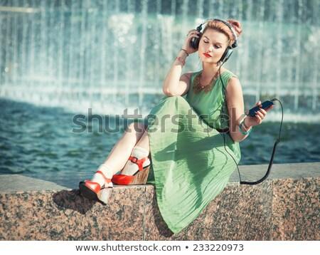 mooie · brunette · vrouwelijke · luisteren · naar · muziek · mp3-speler · tapijt - stockfoto © deandrobot