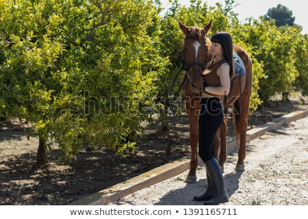 happy beautiful young woman cowgirl taking care of her horse stock photo © deandrobot