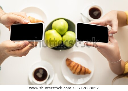 Top view of man drinking coffee near girlfriend stock photo © deandrobot
