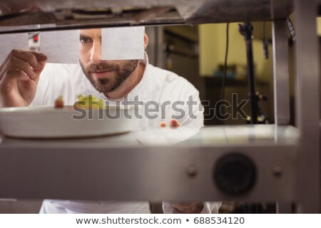 Chef reading his order on sticky note in kitchen counter Stock photo © wavebreak_media