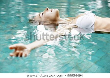 Beautiful woman in white bikini floating in swimming pool Stock photo © wavebreak_media