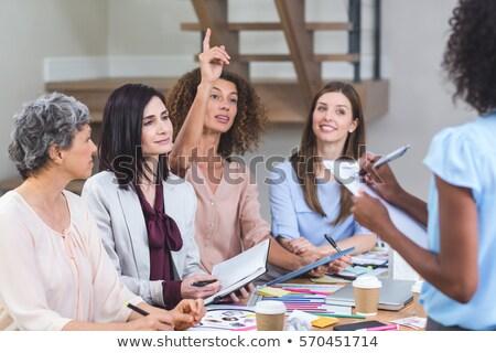 Woman noting on clipboard while colleagues listening presentatio Stock photo © wavebreak_media