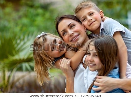 nice family portrait of a mother and her son and daughter hug together stock photo © arleevector
