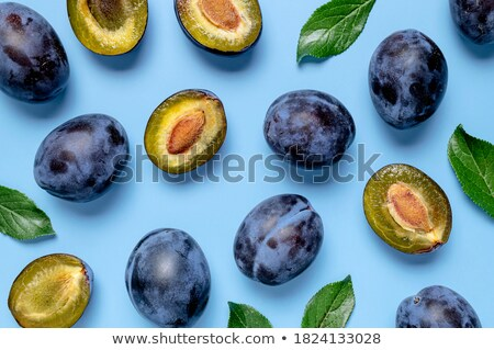 Half a ripe plum with green leaves on a blue background with copy space. Vitamin food. Flat lay Stock photo © artjazz