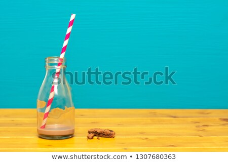 Glass bottle with dregs of chocolate milkshake and a straw Stock photo © sarahdoow
