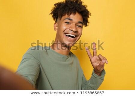 Portrait of funny african man having stylish afro hairdo smiling Stock photo © deandrobot