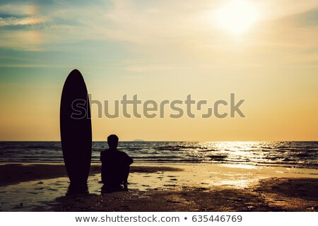Silhouette of surf man sitting with a surfboard on the seashore beach at sunset time Stock photo © galitskaya