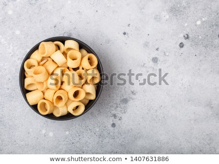 Ready salted potato rings as classic snack in black bowl on light background. Stock photo © DenisMArt