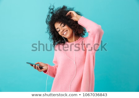 Pleased curly woman in casual clothes and earphones listening music Stock photo © deandrobot
