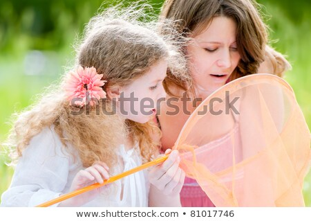 mother and daughter catching butterflies in net stock photo © robuart