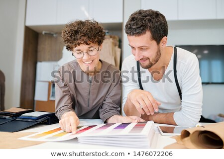 Two young happy fashion designers looking at one of color swatches in catalogue Stock photo © pressmaster