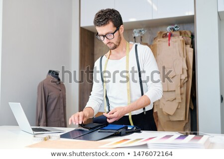 Young tailor in casualwear looking through textile samples in workshop Stock photo © pressmaster