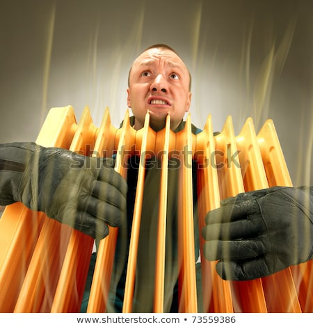 Freezing man holding hot oil radiator Stock photo © nomadsoul1