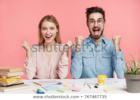 Happy young man rejoices successfully finished work, raises arms, dressed in checkered shirt, being  Stock photo © vkstudio