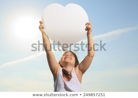 A young child holding heart over the sky Stock photo © Lopolo
