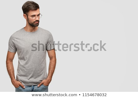 Portrait of serious bearded male with attractive look, keeps fore finger on lips, looks with secret  Stock photo © vkstudio